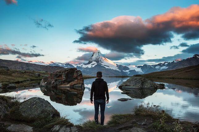 No contact rule is possible: a man standing in front of a lake with beautiful mountains in the backdrop