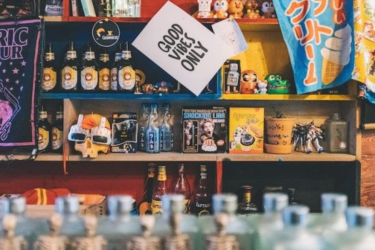 A picture of a shop shelf with the sign 'Good Vibes Only' hanging up