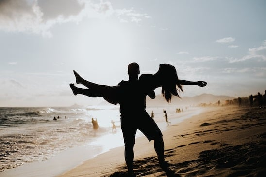 A silhouette of a couple at the beach. The man is holding the woman in the air. She is relaxed and he is strong.