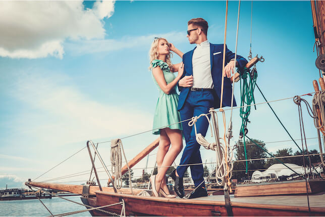 On a sunny day, a couple are standing in a pose on a yacht. He is wearing a smart blue suit, she is wearing a green dress. They stand next to each other, with her hand on his arm.
