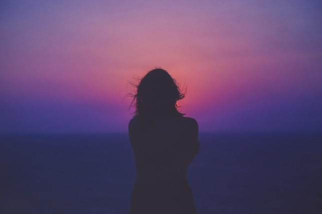 A silhouette of a lady standing against the background of the horizon. Possibly the sea is behind her. There is a sunset.