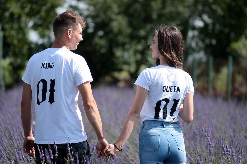 man holding hands with his girl in a field