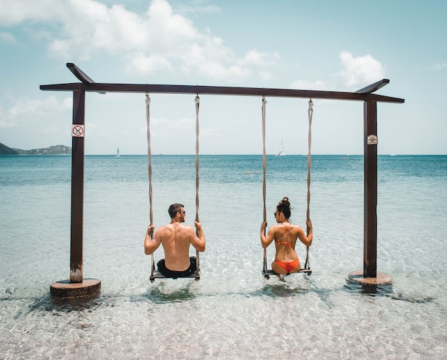 Man and woman on swings on the beach