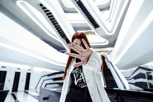 A girl having her photo taken, with her hand playfully covering her face