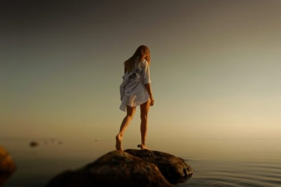 A girl standing on a small rock, looking in to the water below
