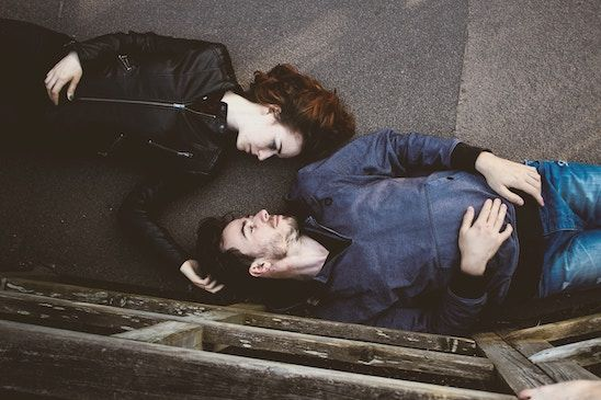 A couple are lying on the ground. Their heads are turned to face each other. Her hand is touching his head.