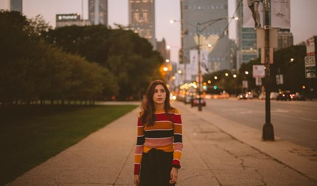 A girl is walking toward you, but she is looking to the right. She is wearing a colourful stripy jumper. In the background you can tell she is in the city.